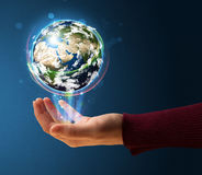 Woman holding a glowing earth globe Stock Photo