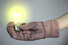 Woman holding a glowing lamp in a glove Royalty Free Stock Photos