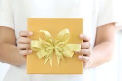 Woman holding a gold gift box. Royalty Free Stock Photos