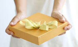 Woman holding a gold gift box Stock Images