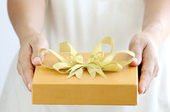 Woman holding a gold gift box Royalty Free Stock Photo