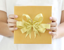 Woman holding a gold gift box Stock Photography