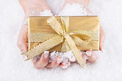 Woman is holding a golden christmas present in her hands - coupo Stock Images