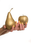 Woman holding a golden fresh pear and apple. Woman wearing stylish yellow nail varnish holding a golden fresh pear and apple in her hands in a conceptual image stock images