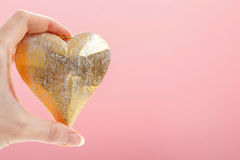 Woman holding golden heart, pink background Stock Photography