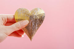 Woman holding golden heart, pink background Royalty Free Stock Image