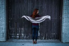 Woman Holding Gray Shawl While Spreading Her Arms Infront of Brown Wooden Door Stock Images