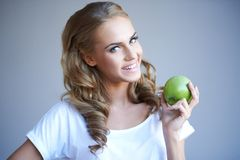 Woman holding green apple against grey stock images