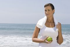 Woman Holding Green Apple At Beach Royalty Free Stock Photos