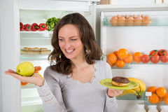 Woman Holding Green Apple And Donut Royalty Free Stock Photography