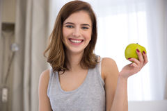 Woman holding green apple at home Stock Photos