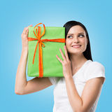 A woman is holding a green gift box. Blue background. Royalty Free Stock Photo
