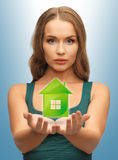 Woman holding green house in her hands Royalty Free Stock Image
