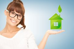 Woman holding green house in her hands Royalty Free Stock Images
