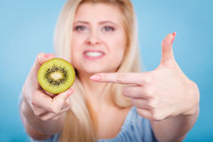 Woman holding green kiwi fruit. Healthy diet, refreshing food full of vitamins. Woman holding sweet delicious green kiwi fruit Stock Photography