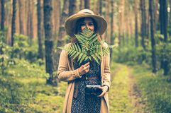 Woman Holding Green Leaf Covering Her Face in the Middle of Woods
