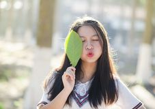 Woman Holding Green Leaf With Lips Kissing and Closing Eyes Royalty Free Stock Image