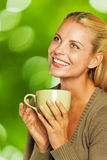 Woman holding a green mug and smiling Stock Photos
