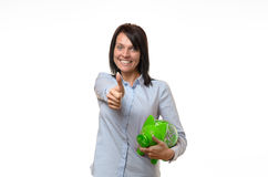 Woman holding green piggy bank with thumbs up. Cute smiling adult woman holding green piggy bank with thumbs up over white background Royalty Free Stock Photos