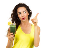 Woman holding green smoothie and pointing. Beautiful healthy woman holding an organic green smoothie and pointing at copy-space. Isolated on white royalty free stock photography