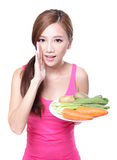 Woman holding green vegetables and carrots Stock Photo