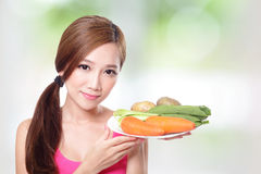 Woman holding green vegetables and carrots Stock Image