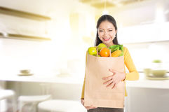 Woman holding groceries bag in kitchen Royalty Free Stock Images