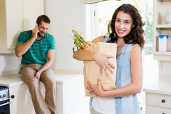 Woman holding groceries while man talking on mobile phone in kitchen Stock Image