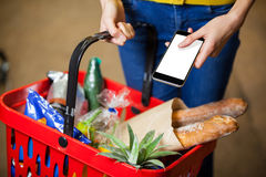 Woman holding groceries and mobile phone in supermarket Stock Photography