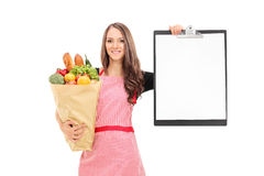 Woman holding grocery bag and a clipboard Stock Photos