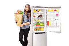 Woman holding a grocery bag by an open fridge. Isolated on white background stock photos