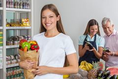 Woman Holding Grocery Bag While People Shopping In Royalty Free Stock Photos