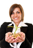 Woman holding a growing plant and coins Royalty Free Stock Photography