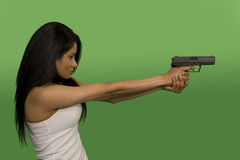 Woman holding gun. Woman holding a gun over green screen Royalty Free Stock Image