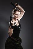 Woman holding gun. On gray royalty free stock photo