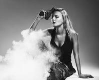 Woman holding gun. Sexy woman holding gun with smoke Stock Image