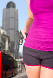 Woman holding gun in hand with london city background Stock Image
