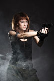 Woman holding gun with smoke Royalty Free Stock Photography