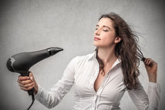 Woman holding a hair dryer Stock Image