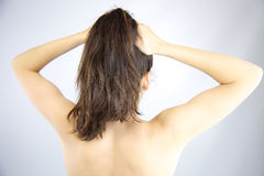 Woman holding hair into ponytail Stock Images