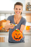 Woman holding halloween bucket and giving trick or treat candy Royalty Free Stock Photos