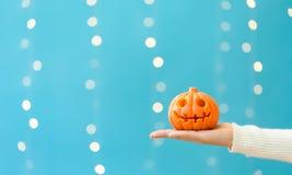Woman holding a halloween pumpkin. On a shiny light blue background Stock Image
