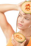 Woman holding halves of cantaloupe. Portrait of young woman holding cantaloupe halves and covering eyes from light isolated on white background royalty free stock photo