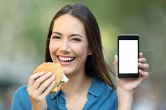 Woman holding a hamburger showing a phone screen Royalty Free Stock Images