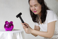 Woman holding hammer over money bank Royalty Free Stock Image