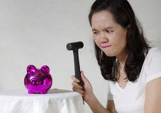 Woman holding hammer over money bank Royalty Free Stock Photography