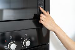 Woman holding hand on black microwave button. Cropped view of woman holding hand on black microwave oven button select program at display, standing in modern stock photos