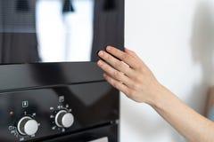 Woman holding hand on black microwave door. Cropped view of woman holding hand at black and opened door modern microwave oven, standing in kitchen stock photography