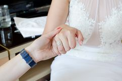 Woman holding hand of a bride. While preparing for the wedding Stock Photo