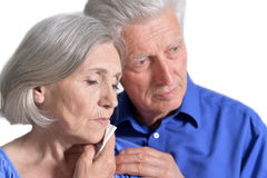 Woman holding hand on cheek. Portrait of sad senior couple, women holding hand on cheek with toothache Stock Images